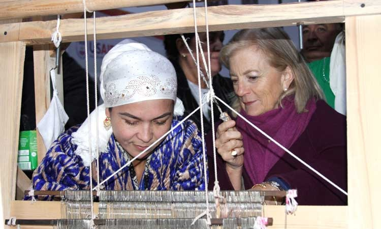 women looking at a loom